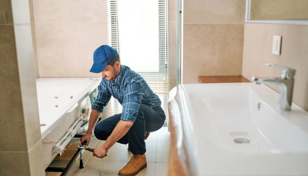 Bathroom renovation being completed by a hanyman wearing a blue hat, blue shirt and pants. He is bent over by the bathtub installing plumbing.