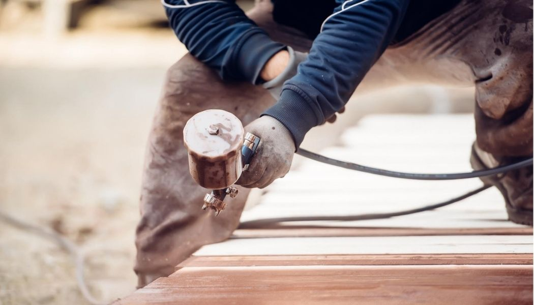 Construction working handyman is spray painting the exterior of a home with a spray gun and wearing a blue shirt and brown work pants.