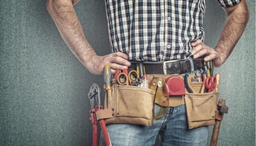 Burnaby Handyman wearing a plad button up shirt with his hand on his hips wearing a construction tool belt.