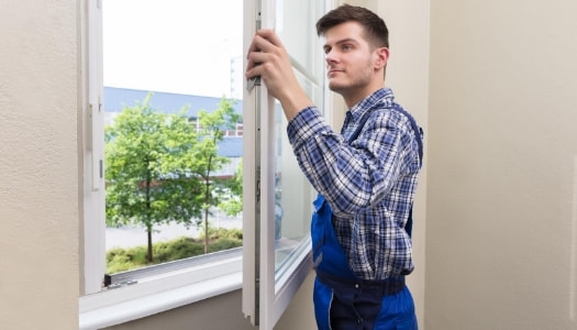 Window installer wearing a checkered blue shirt and blue overalls installing a new replacement window in the home.