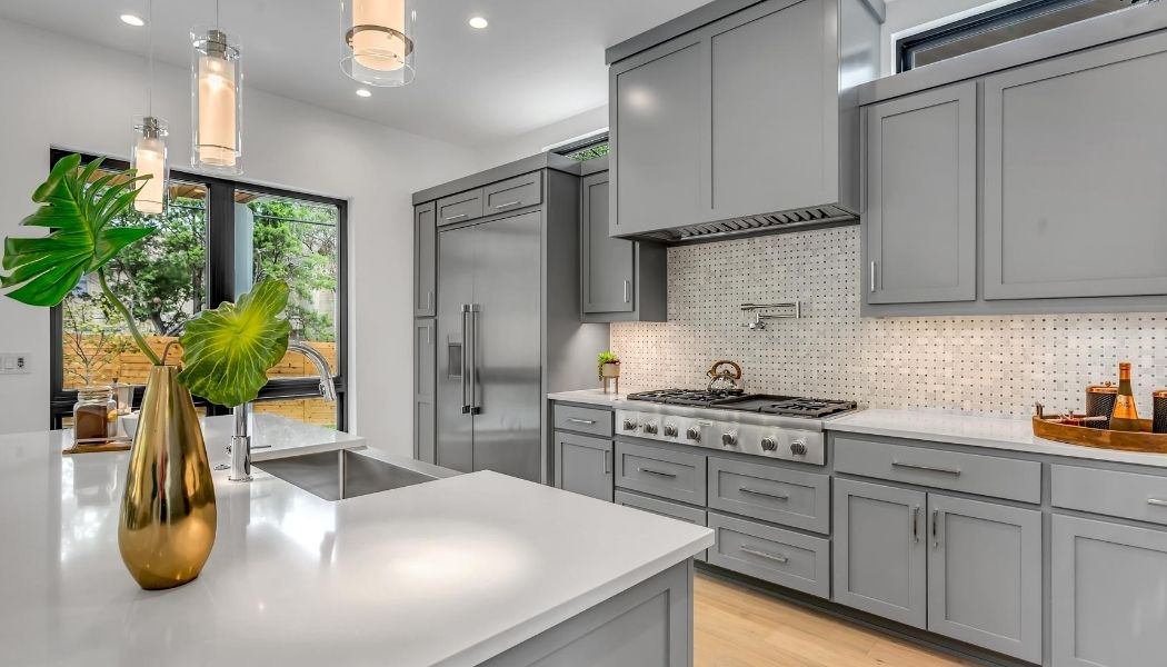 Picture of a fully renovated kitch by Burnaby Handyman using handyman services. The kitchen cabinets are grey and the island has a white counter top and open concept.