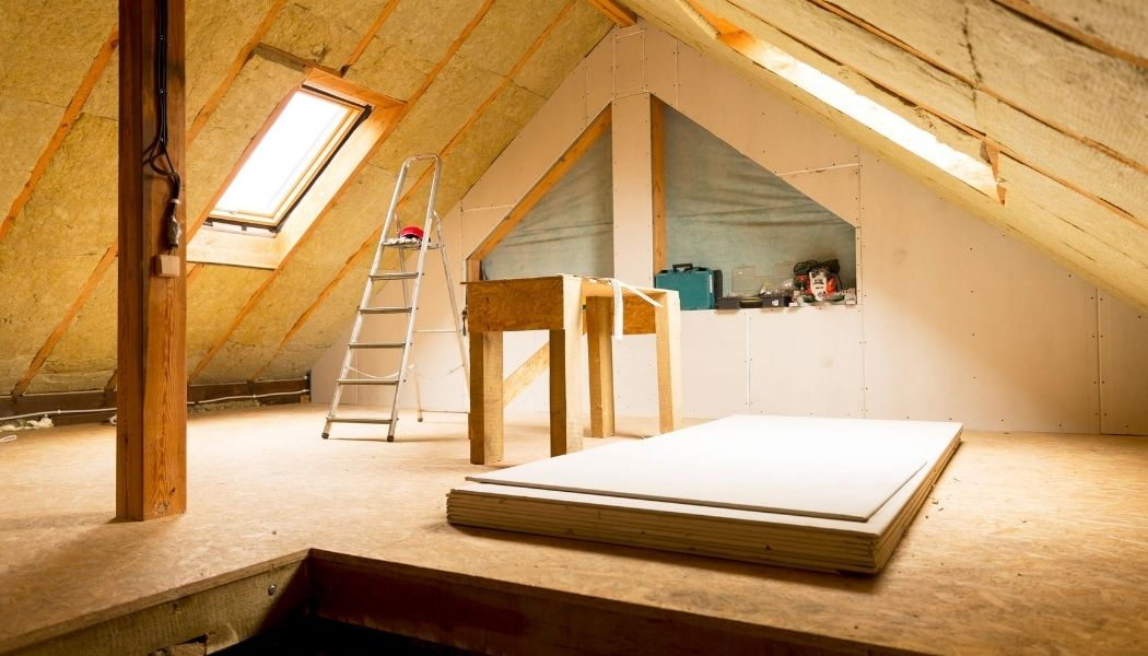 Picture of attic with natural daylight and tools and a ladder in the attic.