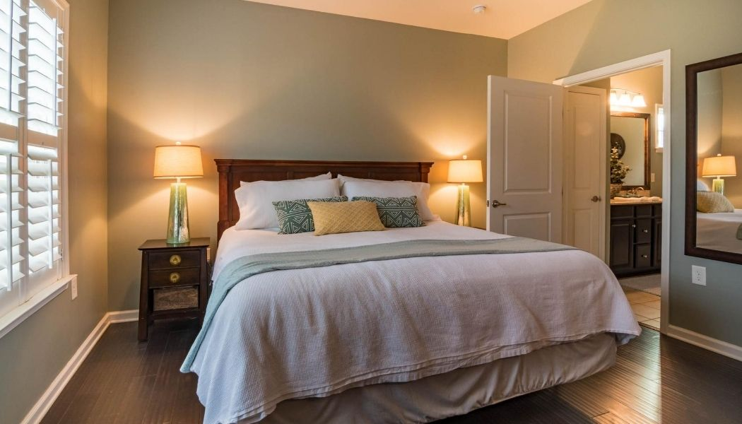 Picture of a fully renovated bedroom with the door open, the bed in the middle and two lights on each side of the bed both turned on.