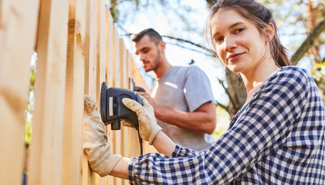 Handywoman and a handyman sanding and refinishing a wood fence. The girl is wearing a plad shirt and the man a grey t-shirt. The girl is wearing gloves and holding a sander smiling.