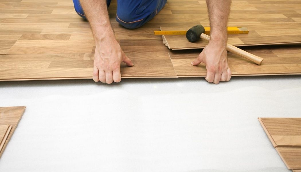 Burnaby Handyman installing wood laminate flooring with a square and a black mallet. The picture shows the man on his knees clicking the pieces into place.